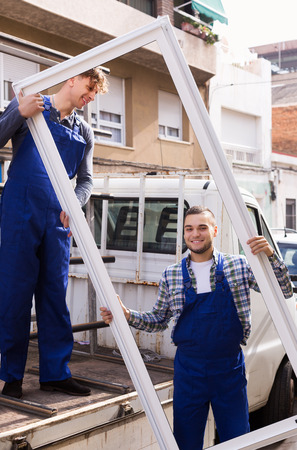 toolroom: Couple of young workers delivering PVC profiles at address