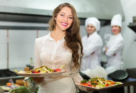 Team of chefs and young beautiful waiter at the restaurant kitchen