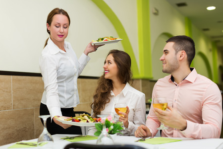 visitors: Positive waitress brings plate with prepared food to visitors table