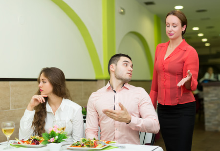 Angry man talking with courteous woman manager in restaurant Stock Photo