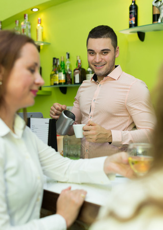 barmen: Two beautiful girls chatting and drinking wine in bar Stock Photo