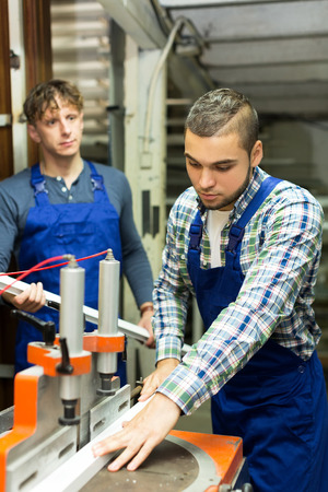 thermoplastic: men working together on a machine in PVC shop