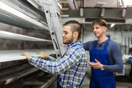 toolroom: Workmen choosing window profiles at factory