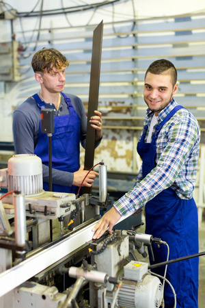 thermoplastic: Two workers working on a machine at modern factory Stock Photo