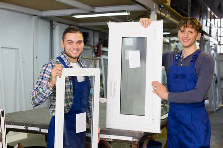 glasswear: Positive workmen together inspecting  windows production at modern plant