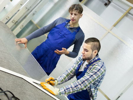 toolroom: Two careful  males cutting glass for windows at workshop