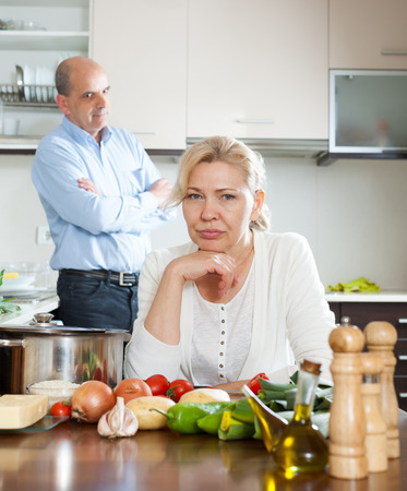 conflicted: Senior mature couple conflicted at home kitchen
