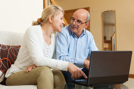 Smiling mature couple  with laptop  at table in home photo