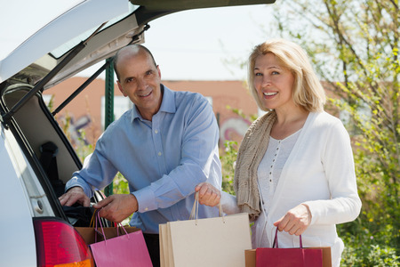 Smiling senior couple with bags near car at shopping center parking lot photo