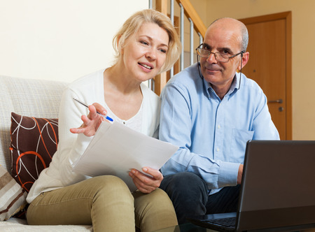 Smiling mature couple with financial documents and notebook in home interior Stock Photo