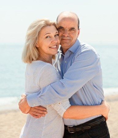 Happy aged lovers hugging outdoor on seaside photo