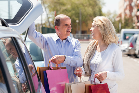 car parking: Happy elderly couple putting shopping bags in car