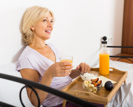 mature woman enjoying  breakfast in bed photo