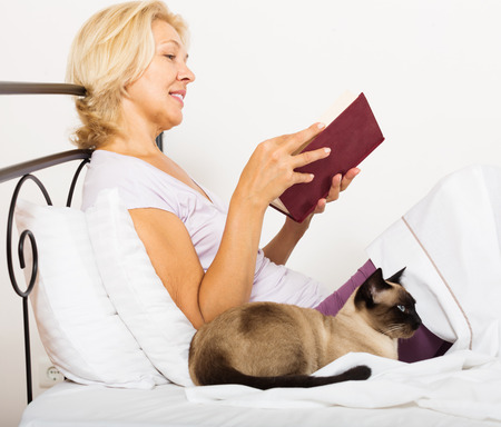 Happy female pensioner with cat reading book and smiling in bed photo
