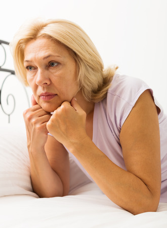 ennui: Sad mature woman with head reclined upon hands in bed at bedroom