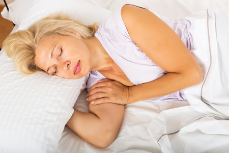 Mature woman in pajamas sleeping with white pillow in bed at home photo