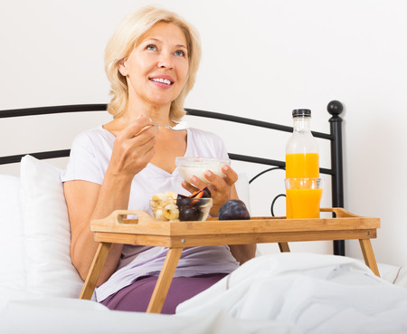 Happy mature woman enjoying healthy breakfast in bedroom photo