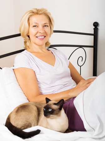 Happy mature woman with kitten resting on bed photo