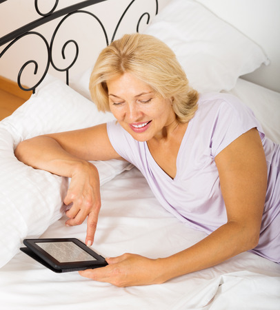 blonde mature woman with eBook laying in  bed photo