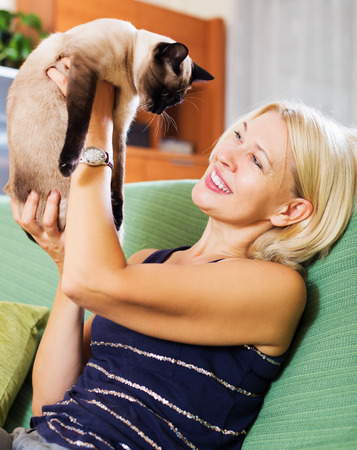 Blond girl sitting on sofa and play with her kitten indoor photo