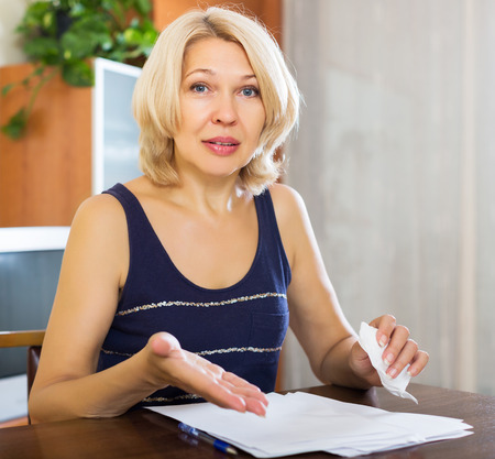 Sad elderly blonde woman filling in financial documents at table in home interior photo