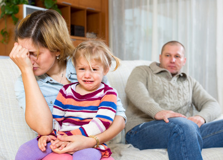 Family conflict. Dismal woman with children against husband after quarrel at home