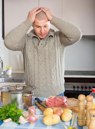 unmarried: Hombre adulto pensativo mirando a la carne y las verduras en la cocina Foto de archivo