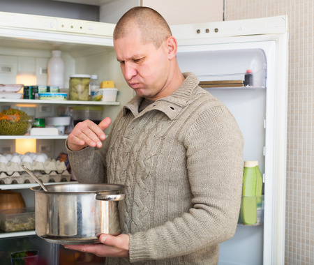 frowy: Man holding foul food near refrigerator