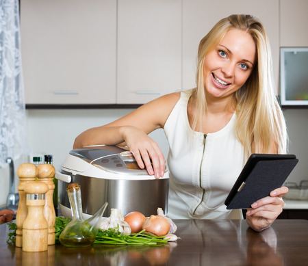 ereader: cheerful housewife reading ereader and cooking with multicooker at home interior