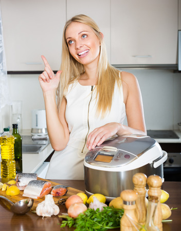 Young blonde woman cooking with new electric multicooker at home photo