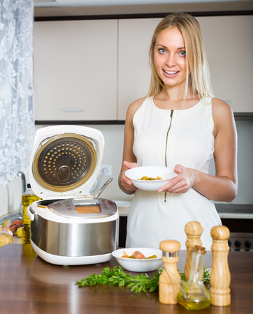 Smiling long-haired housewife cooking with new electric multicooker at home photo