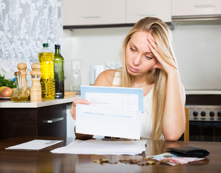 utility payments: Sad blonde housewife filling in utility payments bills at home Stock Photo