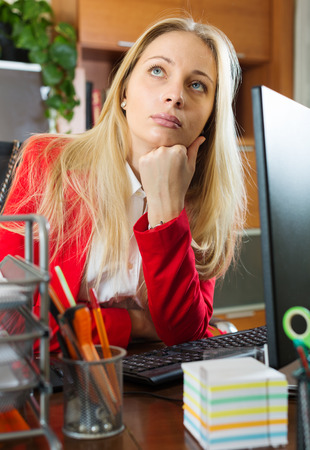tedious: Blonde businesswoman in red having a tedious time at office