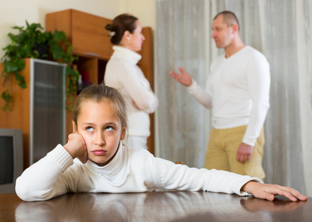 78: Ordinary family of three with little daughter having conflict. Focus on girl Stock Photo