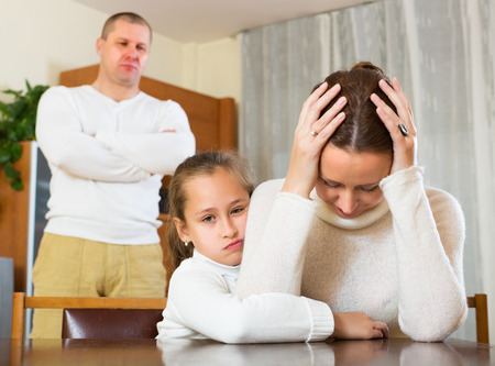 Daughter comforting sad mother in room at home and angry father photo