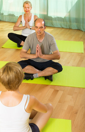 freetime: Mature couple practicing yoga with female instructor. Focus on man