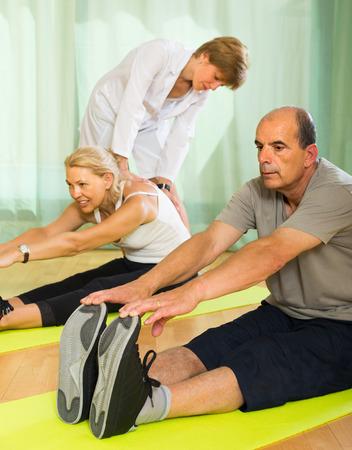 personal medico: El personal m�dico en el gimnasio de ayudar pareja madura de alto nivel para tomar posici�n correcta. Centrarse en el hombre