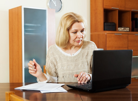 speculate: serious mature woman with notebook and documents at table in office
