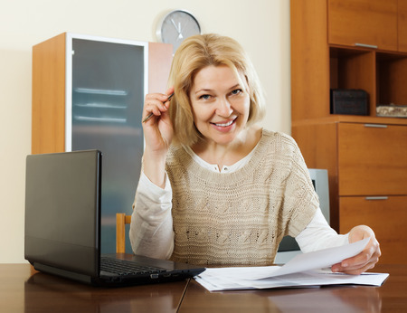 home office interior: Happy mature woman with laptop and financial documents at table in home or office interior Stock Photo