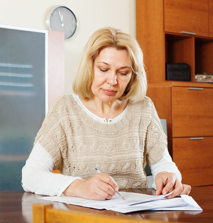 60 something: serious mature woman reading  documents at table