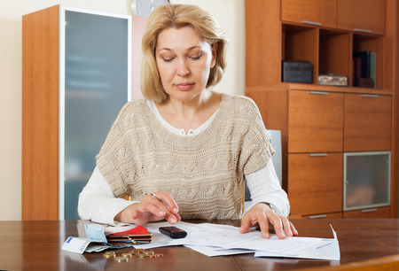 penury: Sad mature woman thinking about the financial issue