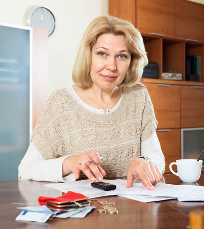 decides: Serious  woman woman working with documents money at  table