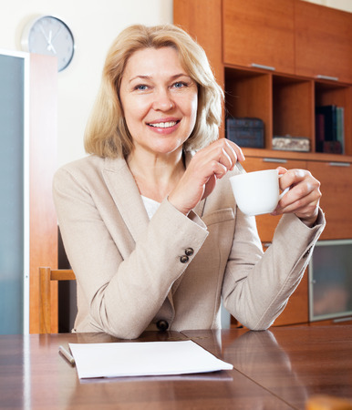 50 something fifty something: happy mature housewife  working with  documents at table in office interior