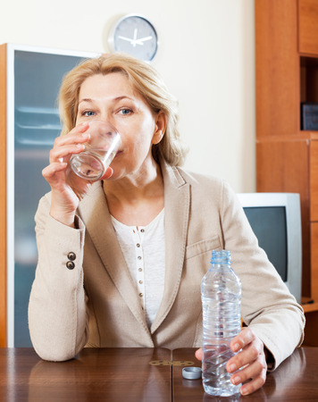 mature businesswoman sitting in the table and drinking fresh water photo