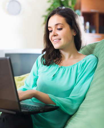 netbook: Young positive woman looking at netbook in living room
