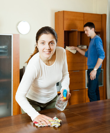 ordinary woman: Ordinary woman with husband cleaning wooden furiture with rag at home