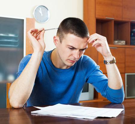 parsimony: Sad thoughtful man filling out financial documents sitting at table in home interior