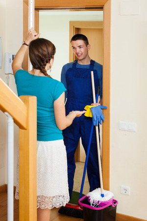 houseman: Housewife meeting cleaner at the door at home