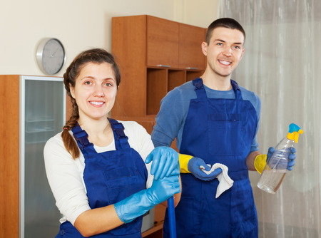 company premises: Happy cleaners cleaning living room at home Stock Photo