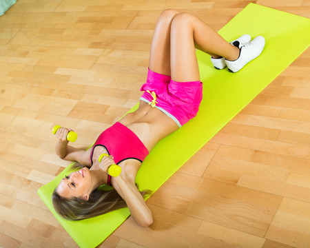 girl working out: Happy girl working out on exercise mat indoor Stock Photo